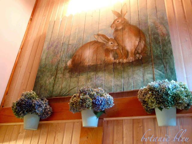 Blue hydrangeas in pale blue metal pots hang beneath hand painted bunnies in stairwell