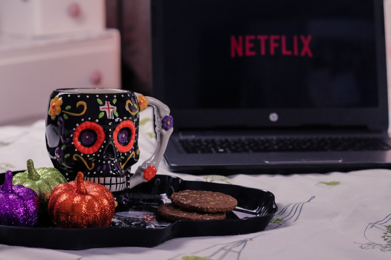 Close up of a sugar skull tea mug on a black skull tray with three pumpkin ornaments next to it, one orange, one green and one purple. The tray is sitting on a bed with a laptop in the background which is blurred as the mug is in focus, taken front on.