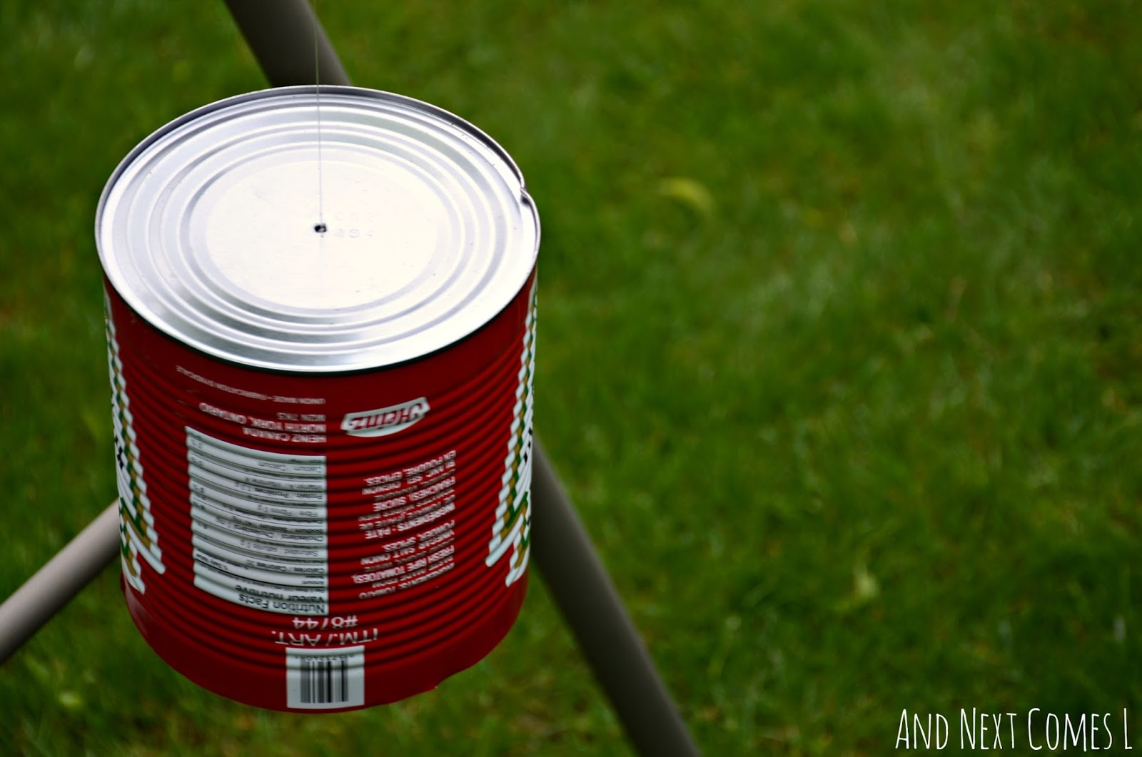 Close up of tin can hanging from a DIY recycled outdoor music station for kids from And Next Comes L