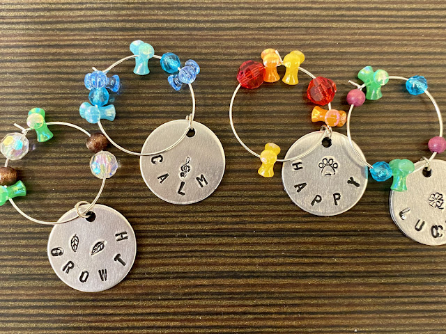 DIY Wine Glass Charms: Women's Craft Night Idea for Make & Take Crafts. Looking for a fun make and take craft project for your women's craft night? These DIY wine glass charms are a fun adult craft for every skill level! An easy and fun adult craft night idea for women of all skill levels, this project is perfect for a wine and art night with friends. Pair your event with your favorite bottle of wine and a good time is guaranteed! Learn how to use metal stamping to make wine glass charms.