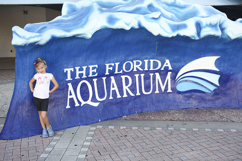 Little girl stands in front of The Florida Aquarium sign