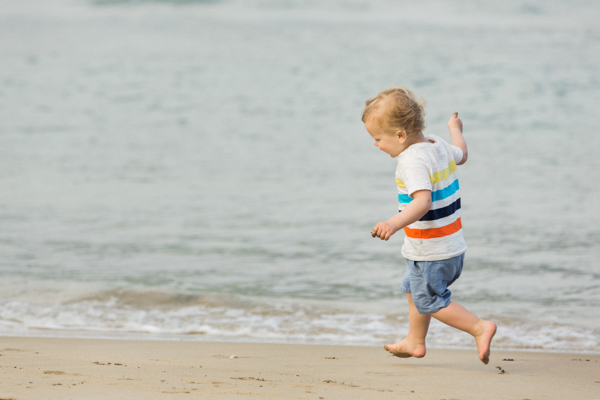 Toddler running & jumping on the sand in Hanalei Bay, Kauai