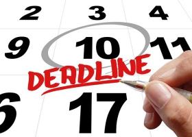 A man drawing a deadline date on a calendar.