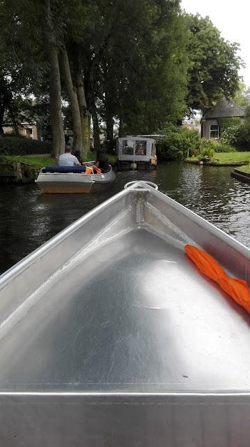 Boeg van varend bootje in Giethoorn, smalle waterstraat.