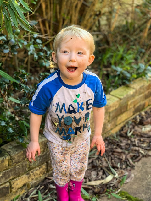 Little in the garden with mud on her trousers, top, hands and chin