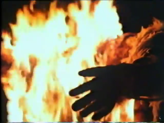 Image from Night of the Demon (1980) showing a fire and the hand of a bigfoot effigy