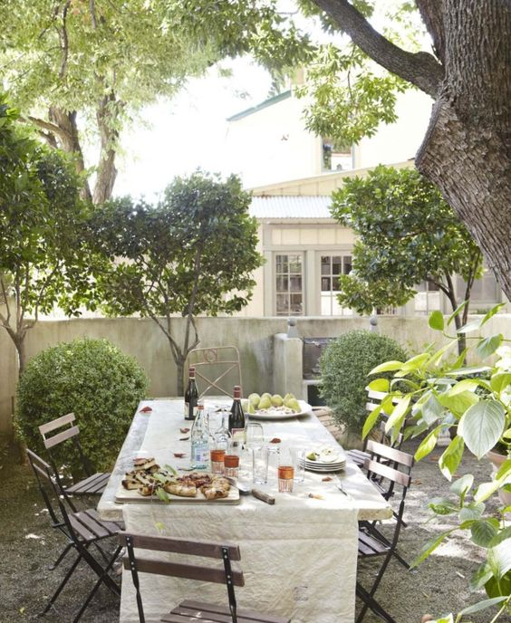 Ivy covered California home of Myra Hoefer with lush gardens and French inspired interiors. #frenchcourtyard #bistrochairs #peagravel