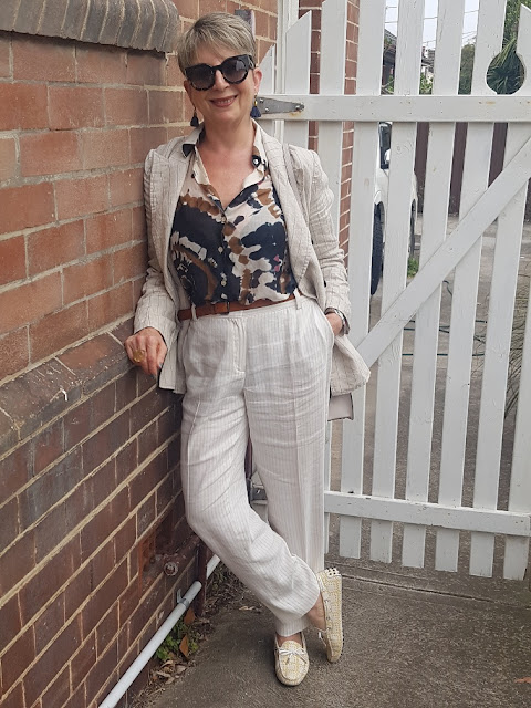Thinking of Italy:  tan colour linen pants a blazer with multi-coloured blouse and a pair of loafers
