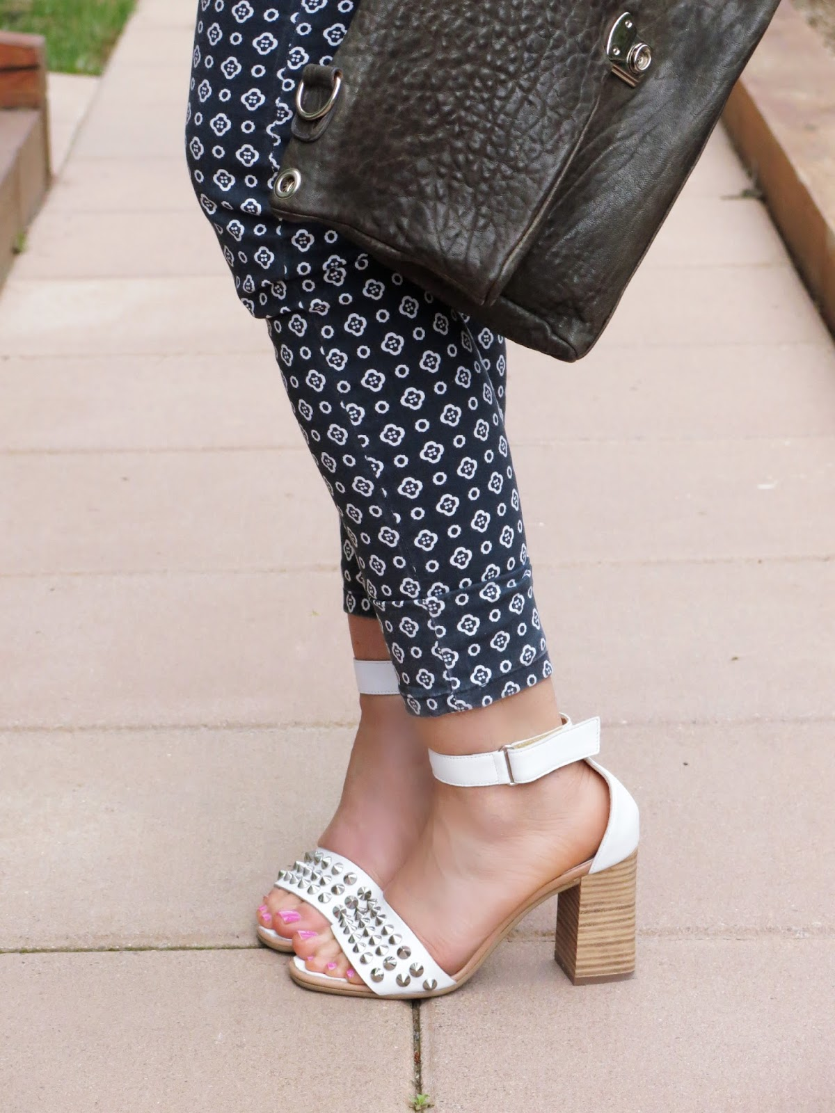 patterned jeans, white ankle-strap sandals, slate blue clutch