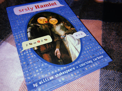 a book called srsly hamlet lying on a blanket