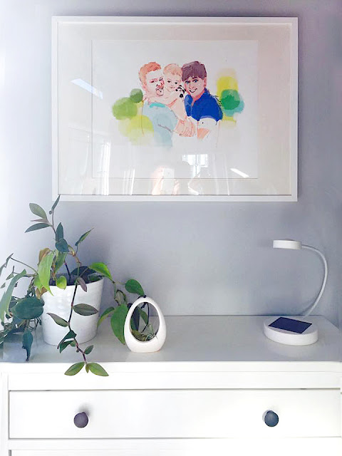 Ikea home decor, white wood framed custom art print with Ikea white table, gay parents, two daddies, daddy and son, baby in parents' arms with panda Benda, fashion illustration, love is love, love wins, LGBTQ family portrait, man in blue, pride