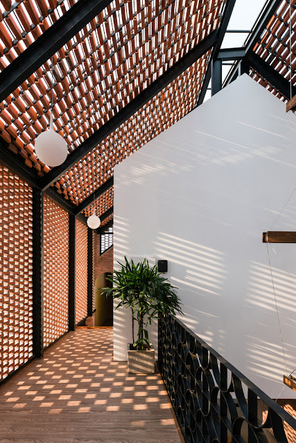 vestibule hallway with spaced bricks to create playful light patterns in hallway, milk glass globe light