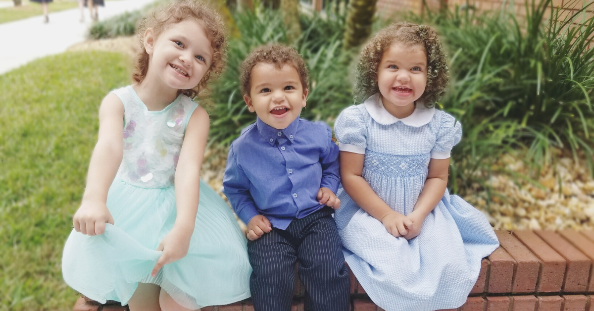 Three curly-haired toddlers sitting together. The girl on the left has a light teal dress on. The boy in the middle is in an all navy blue suit. The girl on the right is in a light blue dress.