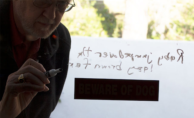 Resident Astronomer tries writing on transparent blackboard (Source: Palmia Observatory)