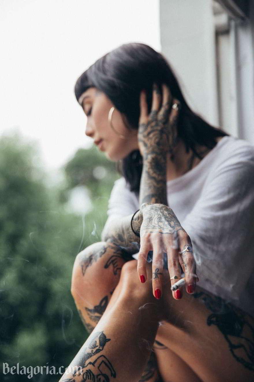 Una preciosa mujer con tatuajes sencillos en las manos está fumando en un balcón mientras mira pasar el día