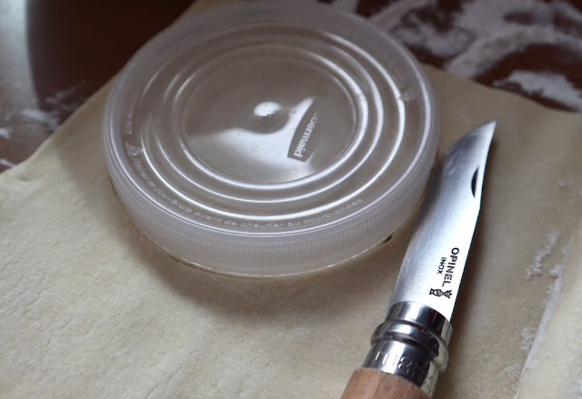 plastic lid on top of puff pastry and knife for cutting