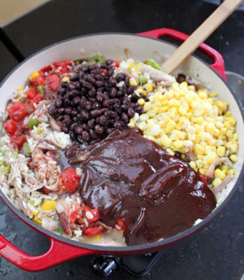 adding beans, bbq sauce and corn to the skillet