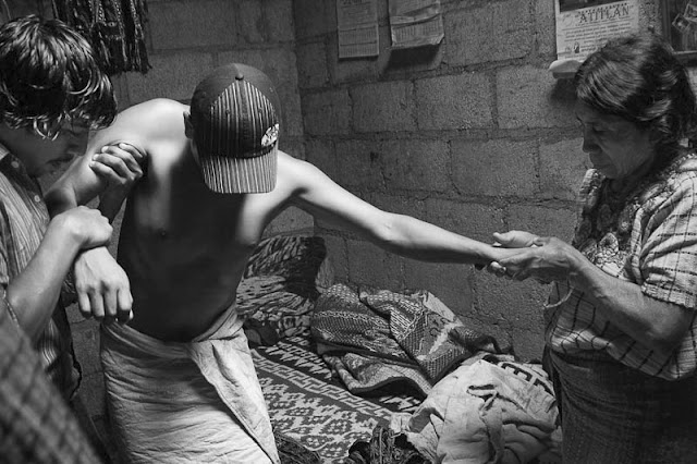 Pedro Mendoza attempting to walk after a healing with the aid of his mother and a friend.© Fran Antmann