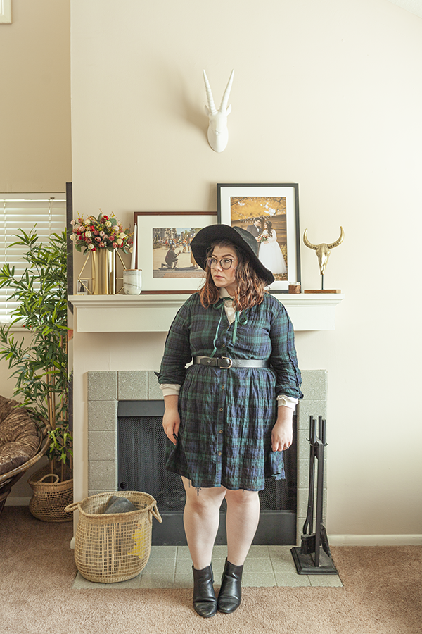An outfit consisting of a black wide brim floppy hat, a white peter pan collar layered under a forest green and navy blue plaid dress belted with a black belt and black chelsea boots.
