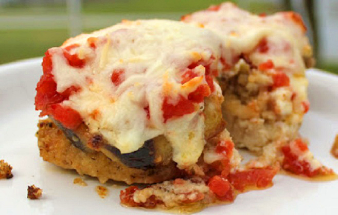 this is a photo of chicken stacked with eggplant, fresh tomato, ricotta cheese and baked on a white plate