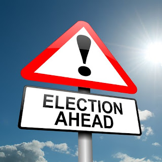 "Triangular sign, white, with a red border and a black exclamation point on it. White rectangular sign directly beneath says ""Election Ahead"" in black uppercase letters. - Canadians with Disabilities Act"