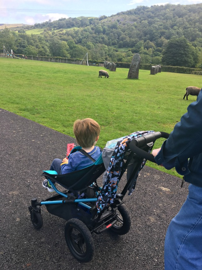 boy-sat-in-Micralite-Festival-Fastfold-Stroller-on-path-with-sheep-and-standing-stones-in-background
