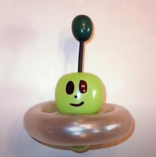 Ufo mit Alien aus Luftballons geformt.
