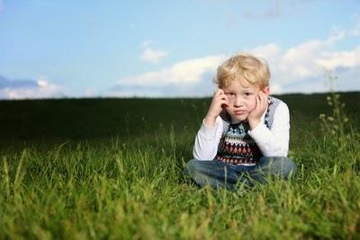 Kind sitzt traurig auf einer Wiese