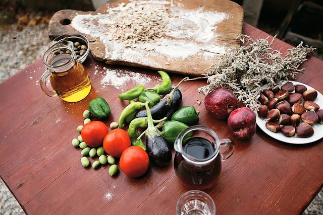 Cibo sul tavolo, peperoni, melanzane, olio d'oliva, zucca, castagne, vino, mele, pomodori, avena, rosmarino