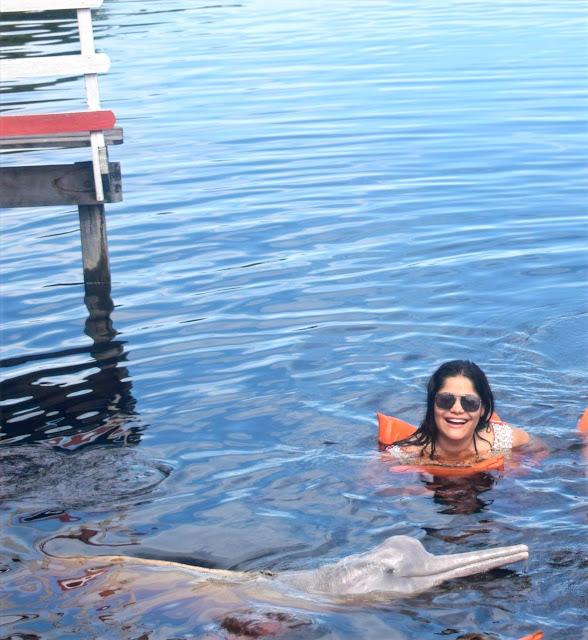 mulher nadando no rio com um boto