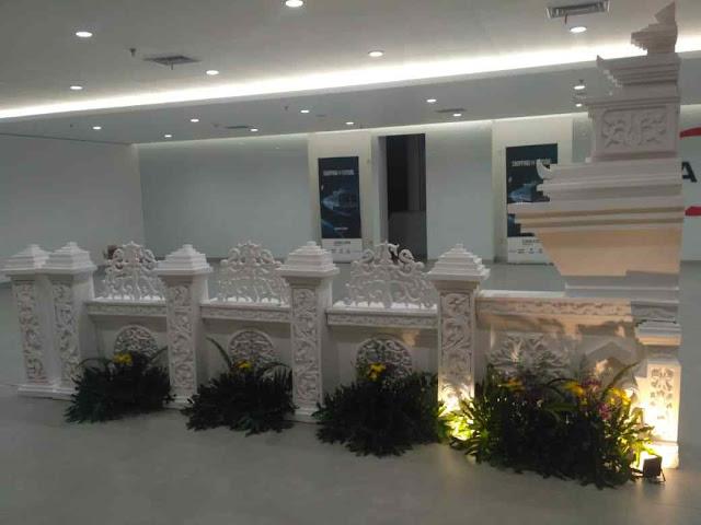 Dekorasi ukiran busa gabus styrofoam dengan tema dan motif Bali nusantara, gapura yang dihias bunga daun mini garden pakai lighting lampu untuk event grand launching kantor perusahaan.
