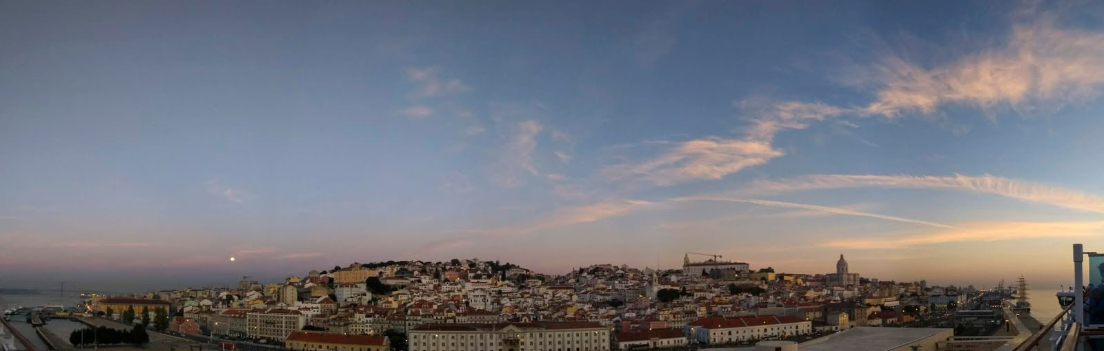 A panorama of the moon setting over Lisbon at sunrise.