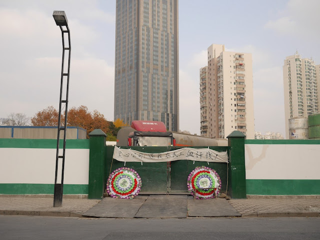 "two Chinese funeral wreaths and banner with ""黑心公司:还我农民工血汗钱"" on an entrance to a construction site in Shanghai"