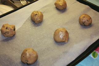 six balls of raw cookie dough lying on a baking sheet on a baking tray, ready to go into the oven