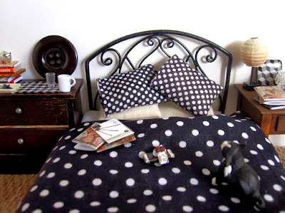 One-twelfth scale modern miniature bedroom in black, white, beige and wood. On the bed is a cat, a bar of chocolate and a pile of magazines.