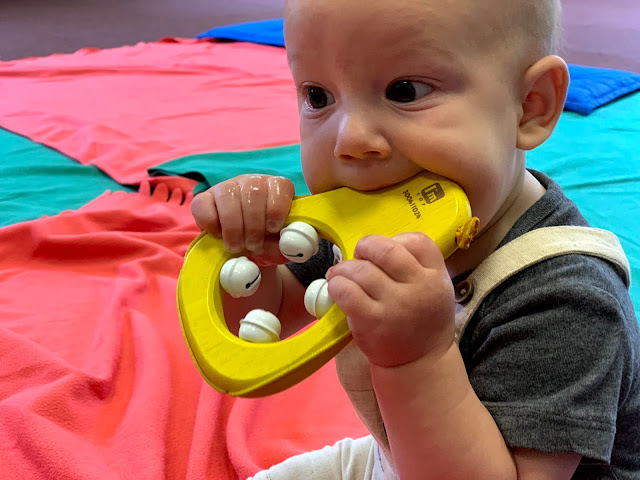 6 month old baby boy eating a bell toy in a music class