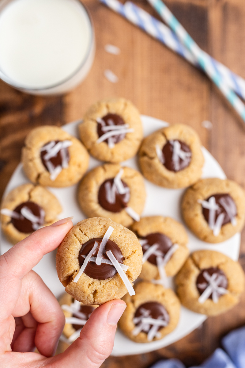 Over head photo of a hand holding a Keto Chocolate Thumbprint Cookies above a plate full of them on a wooden table.