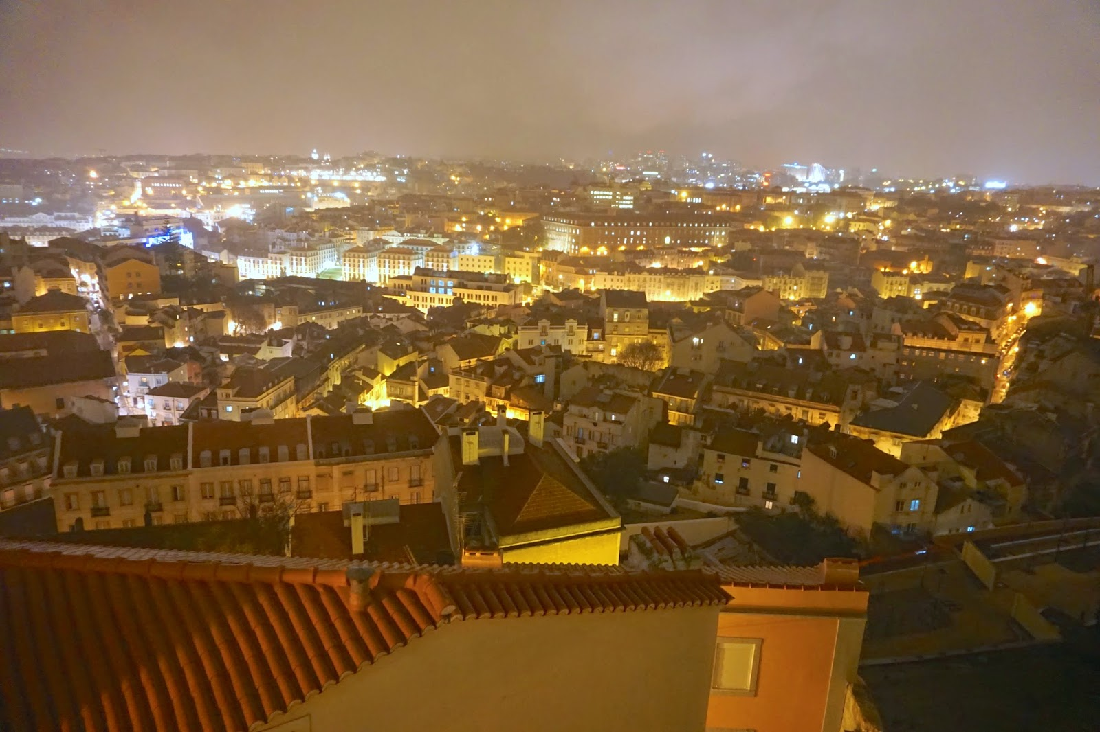 View from the balcony of Miradouro Da Graca at night in Lisbon overlooking the city lights