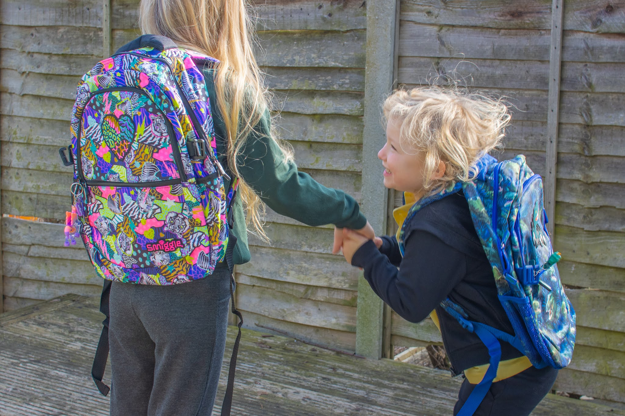 Two sisters standing next to each other in school uniform, the younger one is jumping up and down. They both have Smiggle Galaxy Attach backpacks on received to review.