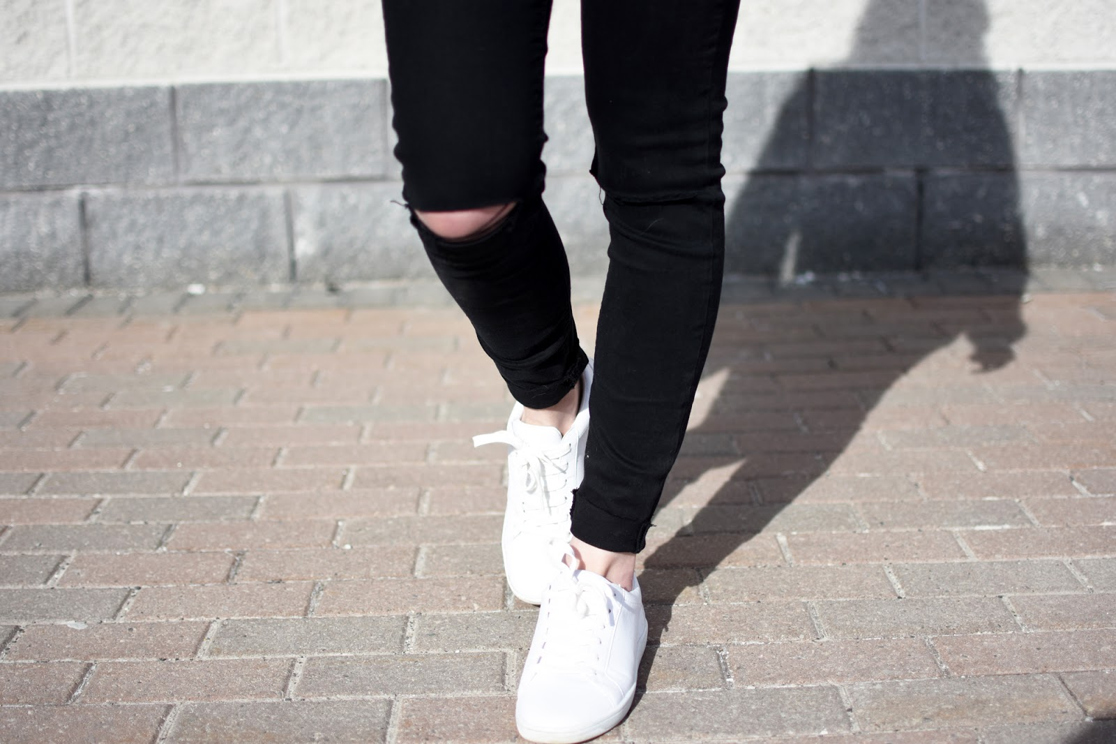 Black skinny jeans and white sneakers, both from Zara
