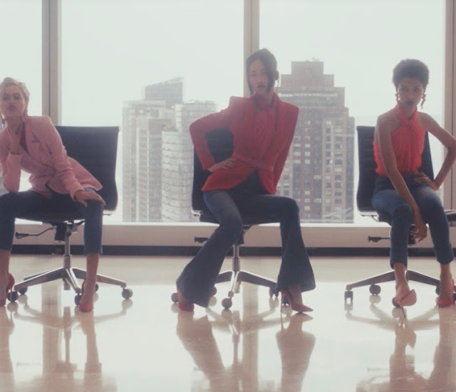 Women in suits on office rolling chairs in Vogue office