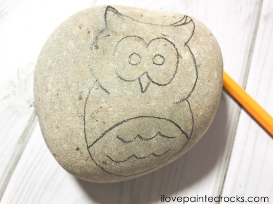 using a pencil to draw an owl onto a rock