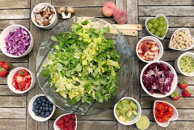 Large bowl of lettuce surrounded by several smaller bowls of assorted fruits and vegetables