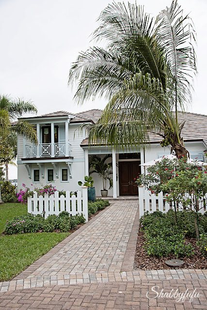 The front of the HGTV Dream Home 2016. A white picket fence, palm trees, and beautiful brick walkway.