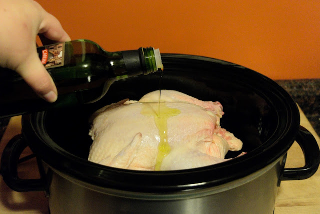 Olive oil being drizzled over the whole chicken in the crock pot.