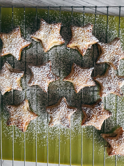 Baked stars on a wire tray with icing sugar sprinkled over them
