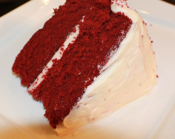 this photo is of red velvet layer cake that are raspberry puree inside of it and red velvet. They have whole raspberries on top and cream cheese frosting in heart paper liners