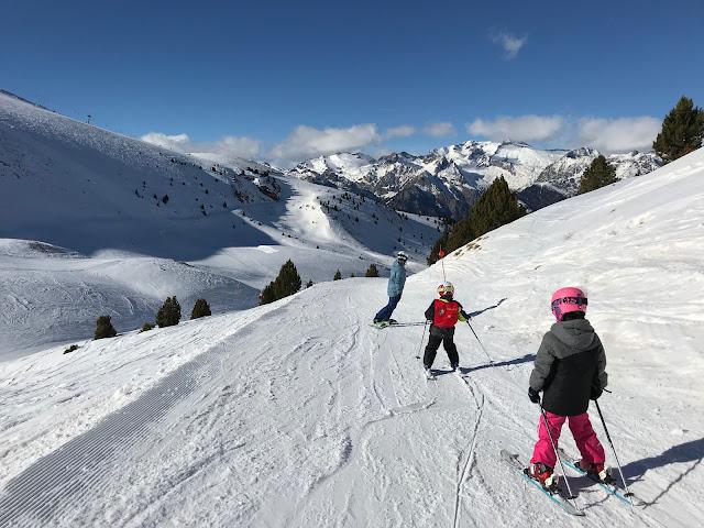 Niños esquiando detrás de su padre