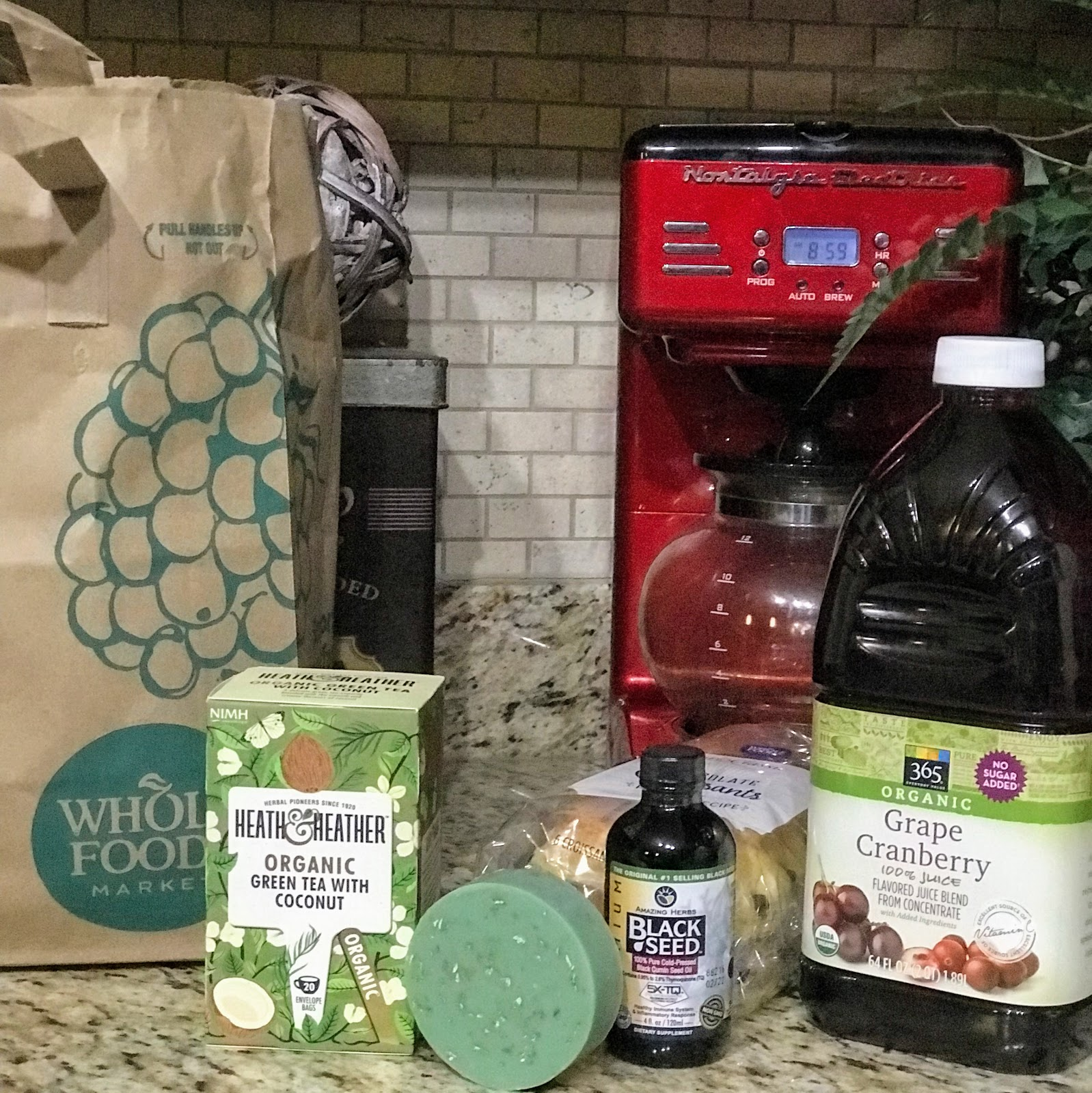 Image: All the items Tangie Bell bought from Whole Foods. She hauled on Bits and Babbles Blog: cranberry juice, black seed oil, soap, tea, bread