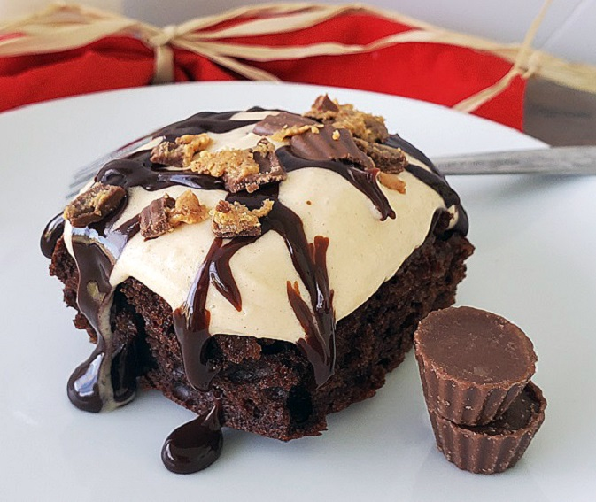 this is called a poke cake and is filled with chocolate peanut butter cream cheese frosting and whipped cream with hot fudge sauce on top and crumbled peanut butter cups